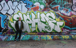 """My Name Is - Graffiti artist Riley Gregor stands next to his work on the legal graffiti wall. """"The more vibrant the colors are, people like it, you know, they like my things and that"""
