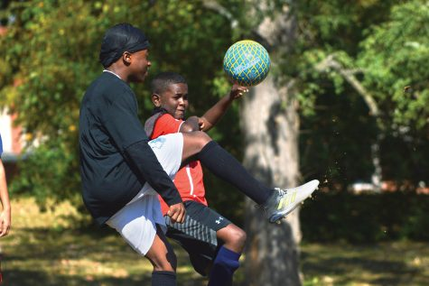 A photo of two boys kicking a soccer ball.