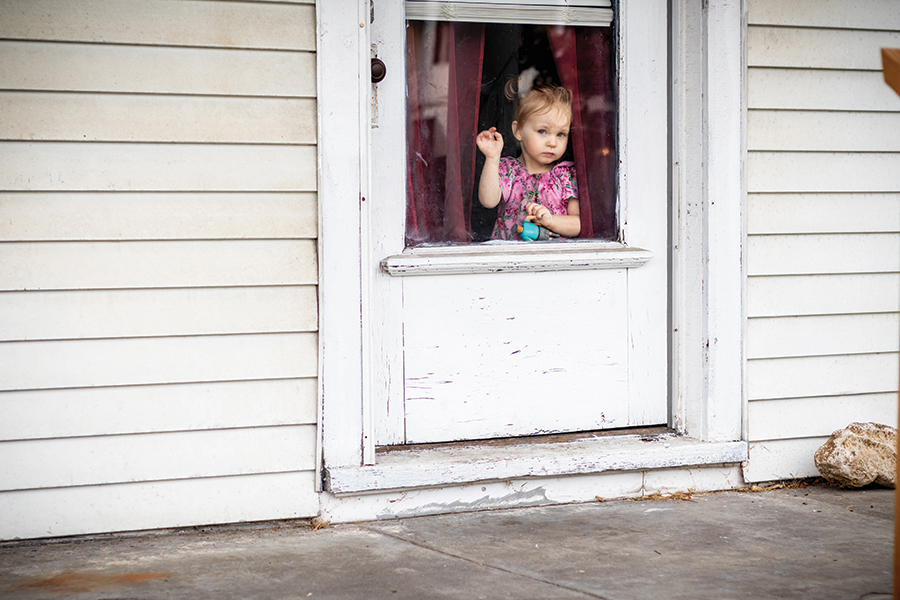 Looking out the front door of her grandmother's house in the Oakdale neighborhood near Churchill Downs, one-year-old Roxanne (Roxy) Price watches pedestrians and traffic on the road on Oct. 16. Just outside the doorframe and on the windows, columns, and the roof hid the danger beneath the cracked paint that caused Roxy to get lead poisoning.