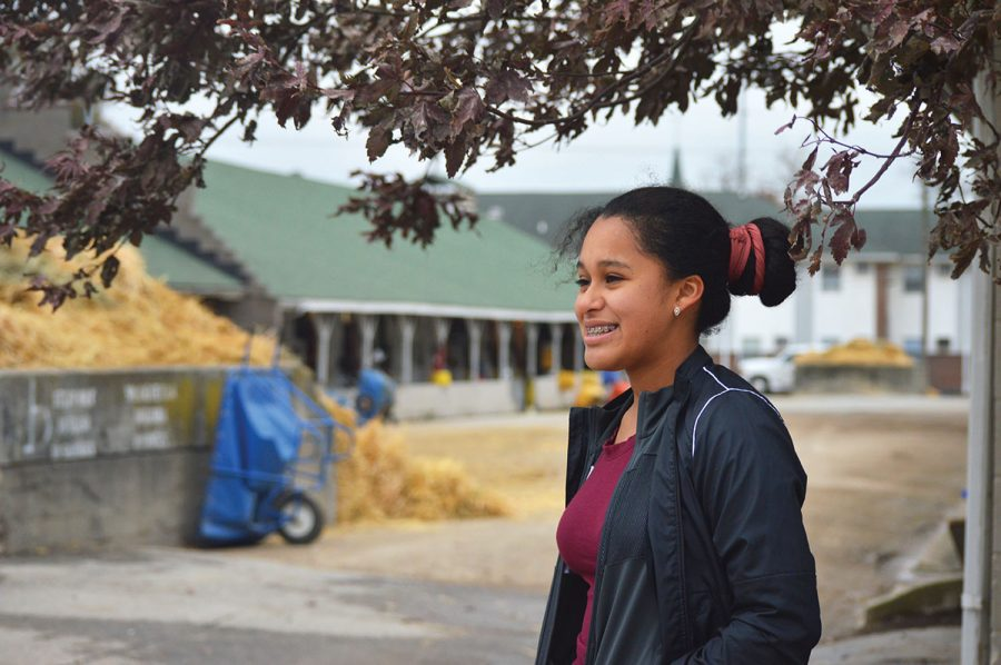 A photo of a young woman smiling in front of the stables inside of Churchill Downs. The young woman is part of the Backside Learning Center.