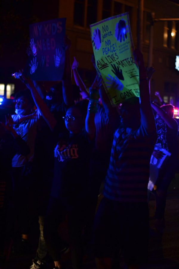 """No Justice, No Peace - Standing at the intersection of Eastern Parkway and Bardstown Road, protesters illuminated by the flashing lights of the police cars in front of them raise their hands, some calling out, """"Don't shoot,"""" on May 30, 2020."""